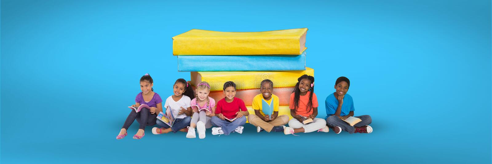 Children sitting on the floor and a pile of books with blue background royalty free stock photo