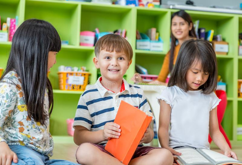 Children sitting on floor and reading tale book in preschool li stock image