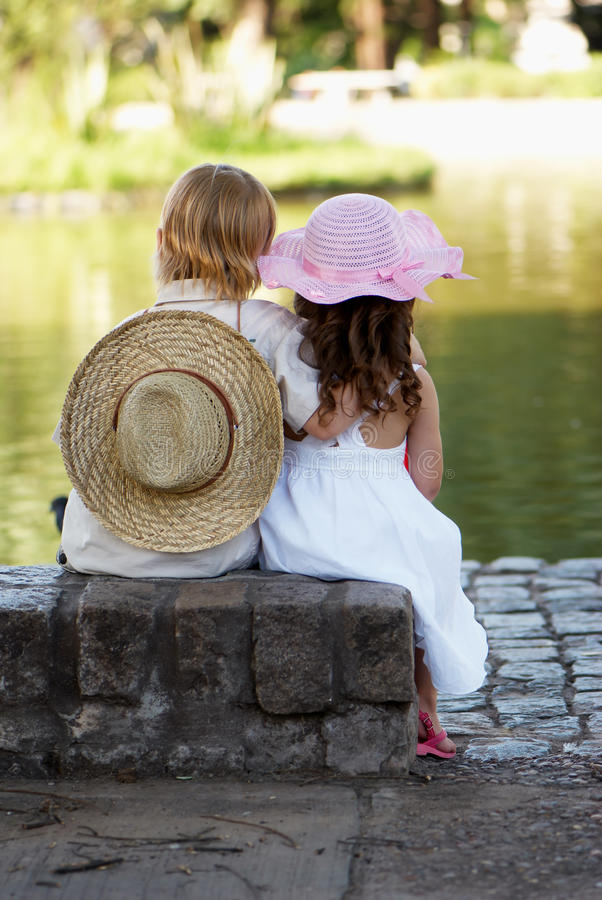 Free Children Sitting On The Bank Of Lake Royalty Free Stock Image - 14691546