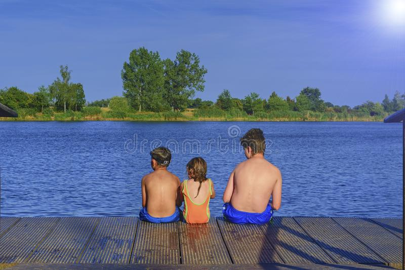 Children sitting on pier. Three children of different age - teenager boy, elementary age boy and preschool girl sitting. On a wooden pier. Summer and childhood stock images