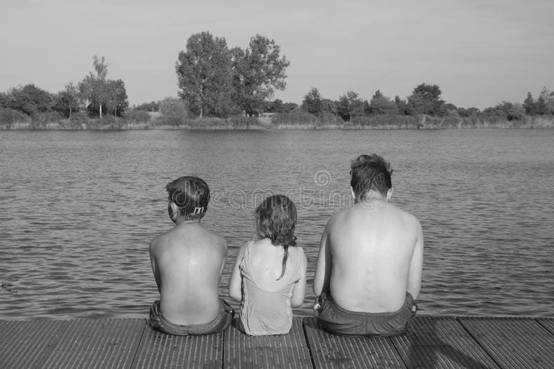 Children sitting on pier. Three children of different age - teenager boy, elementary age boy and preschool girl sitting. On a wooden pier. Summer and childhood royalty free stock photo
