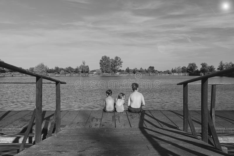 Children sitting on pier. Three children of different age - teenager boy, elementary age boy and preschool girl sitting. On a wooden pier. Summer and childhood stock photography