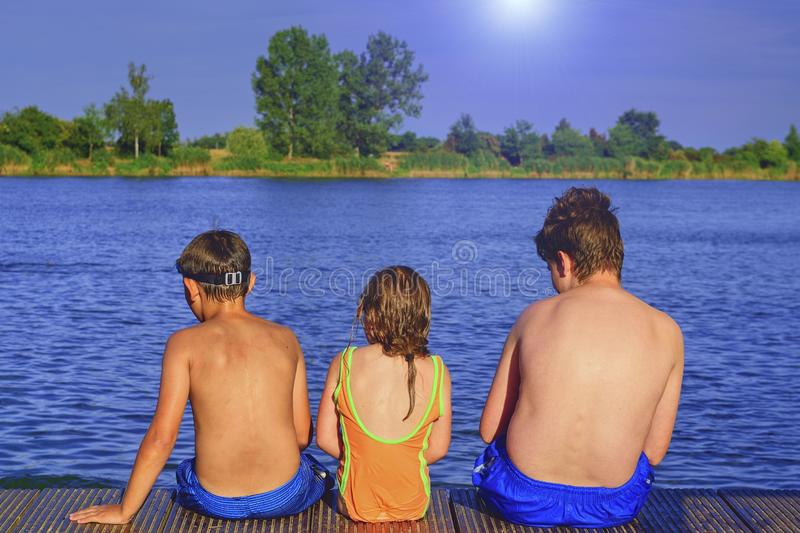 Children sitting on pier. Three children of different age - teenager boy, elementary age boy and preschool girl sitting. On a wooden pier. Summer and childhood royalty free stock image