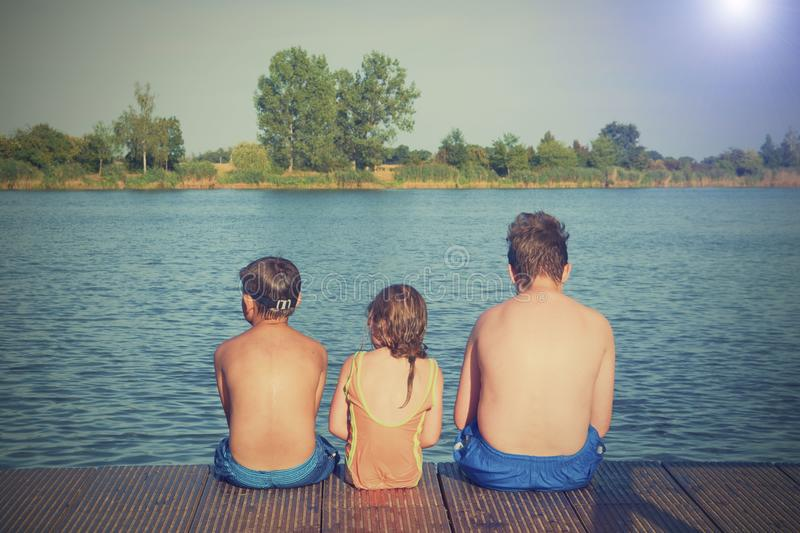 Children sitting on pier. Three children of different age - teenager boy, elementary age boy and preschool girl sitting. On a wooden pier. Summer and childhood stock photos