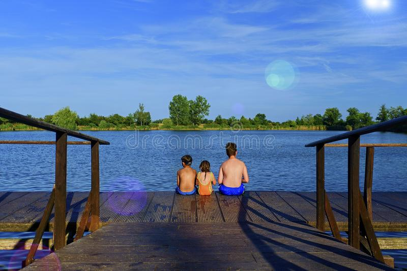 Children sitting on pier. Three children of different age - teenager boy, elementary age boy and preschool girl sitting. On a wooden pier. Summer and childhood royalty free stock photos