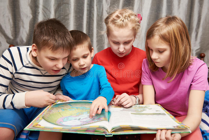 Children sitting and reading geography book. At home royalty free stock image