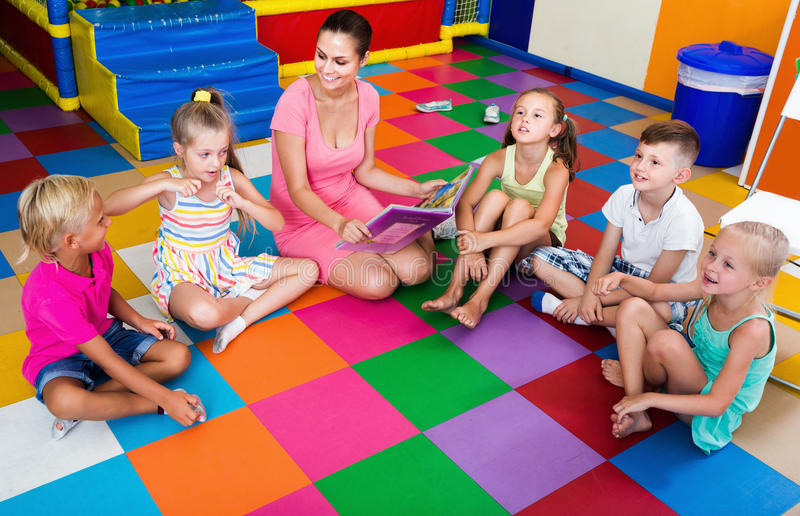 Children sitting with smiling teacher and listening to book stock images