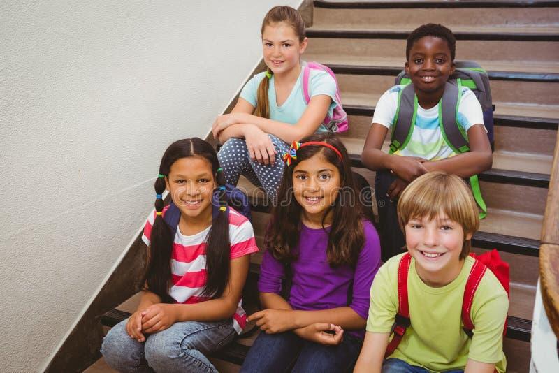 Children sitting on stairs in school stock photo