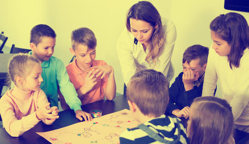 Children sitting at table with board game in classroom royalty free stock photo