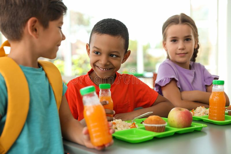 Children sitting at table and eating healthy food during break. At school stock images