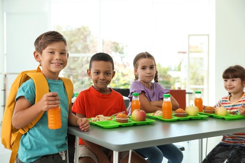 Children sitting at table and eating healthy food. During break at school stock photo