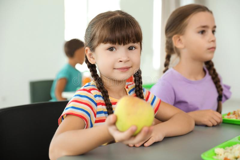 Children sitting at table and eating healthy food stock images
