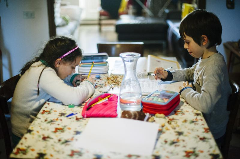 Children sitting at the table at home perform homework stock photos