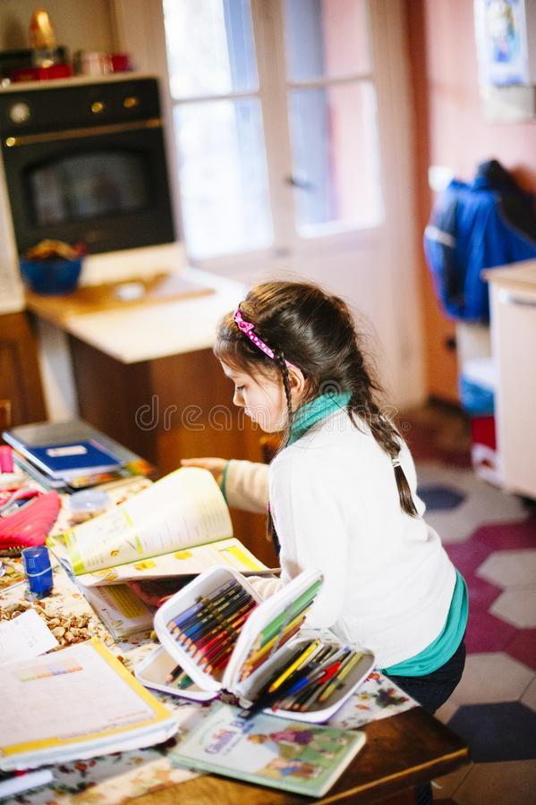 Children sitting at the table at home perform homework stock photo