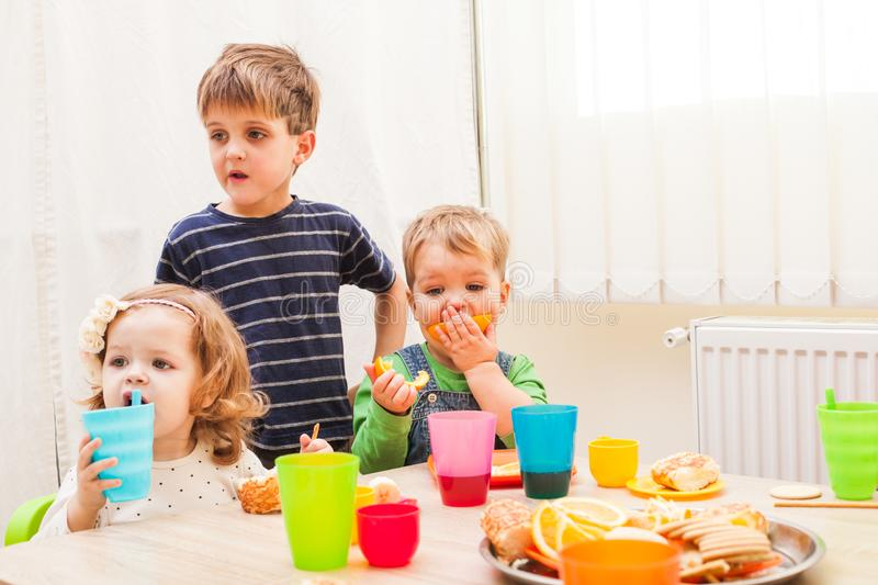 Lunch in kindergarden. Children are sitting at the table with lunch and eating fruits and cakes stock photography