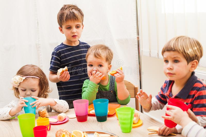 Lunch in kindergarden. Children are sitting at the table with lunch and eating ts and cakes royalty free stock photos