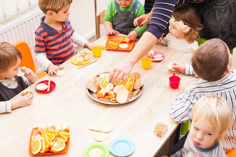 Lunch in kindergarden. Children are sitting at the table with lunch and eating ts and cakes stock photo