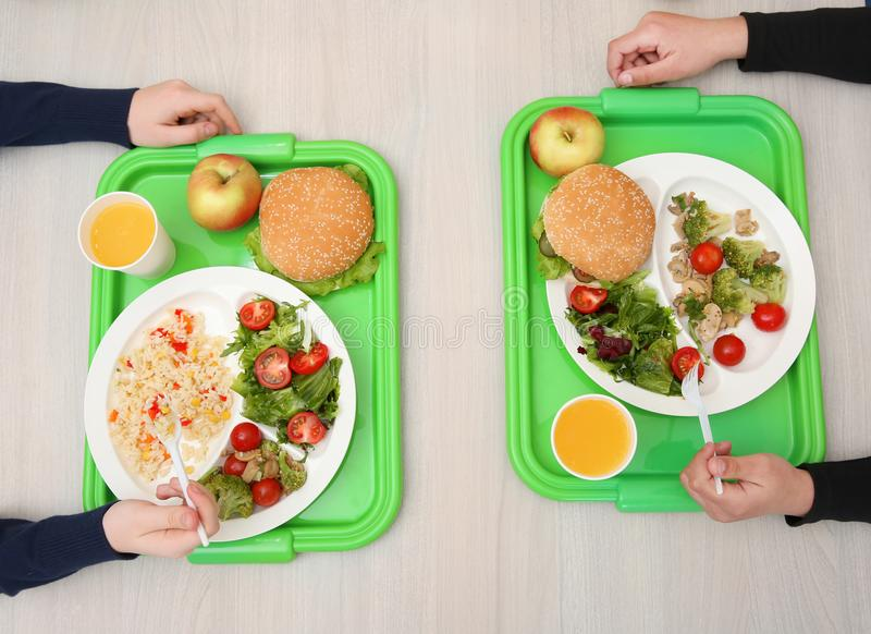 Children sitting at table in school cafeteria stock images