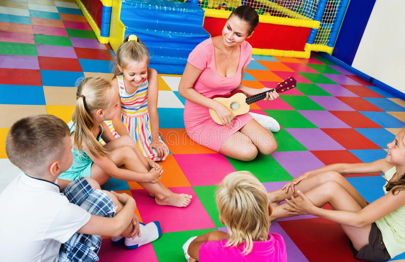 Children sitting with teacher and listening to music in class stock photos