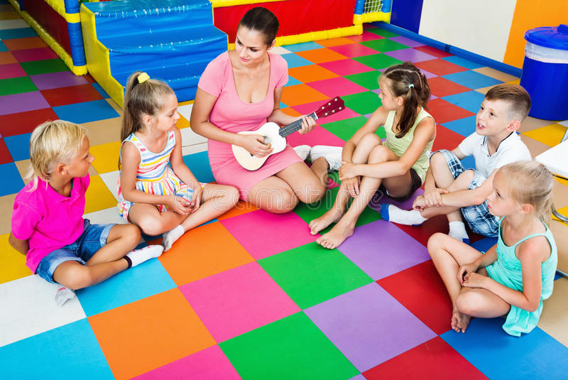 Children sitting with teacher and listening to music in class royalty free stock photos