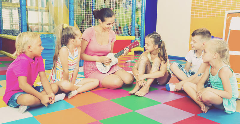 Children sitting with teacher and listening to music in class royalty free stock photo
