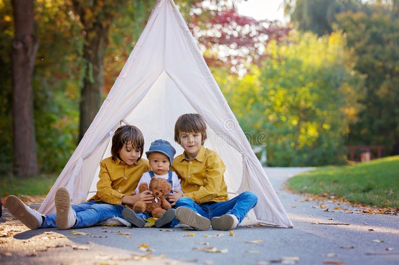 Children, sitting in a tent teepee, holding teddy bear toy with. A nature autumn background in the park, imagination or happiness concept royalty free stock photo