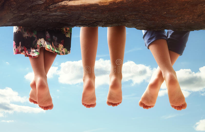 Children sitting in a tree dangling their feet. Three kids sitting in a tree dangling their feet against a blue sky in summer concept for family, friends royalty free stock images