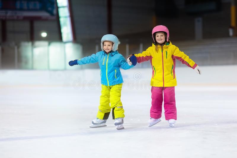Children skating on ice rink. Kids winter sport. Children skating on indoor ice rink. Kids and family healthy winter sport. Boy and girl with ice skates. Active royalty free stock image