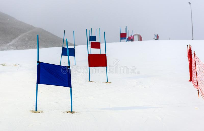 Children skiing slalom racing track with blue and red gates. Small ski race gates on a pole with children skiing in the background royalty free stock photography