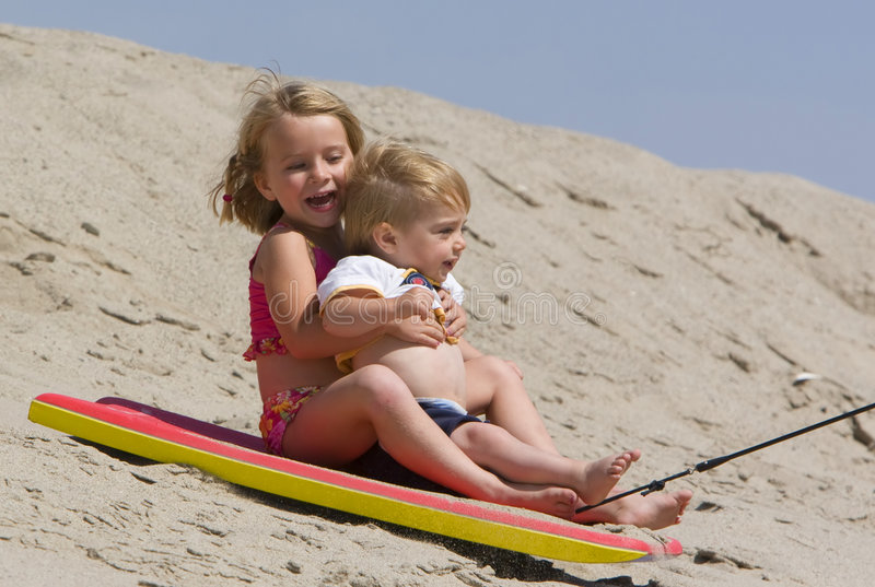 Children sledding down sand dune royalty free stock photo