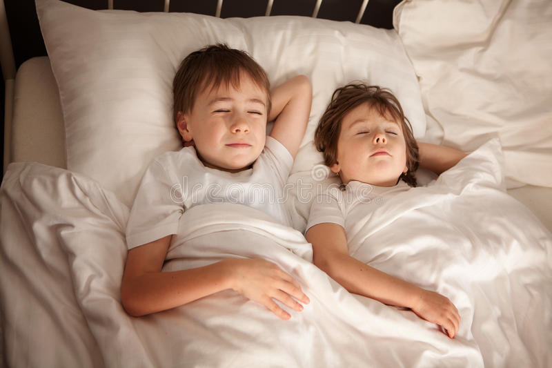 Children sleeping in bed. Cute young preschool brother and sister sleeping together in bed royalty free stock photos