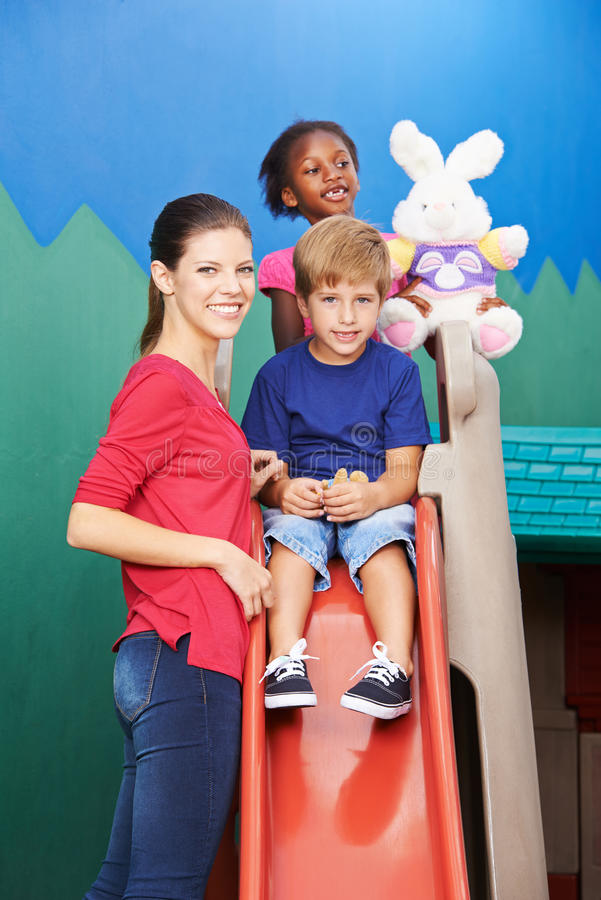 Children sliding on slide in kindergarten stock image