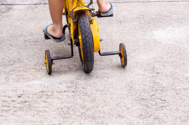 Children with slippers cycling bike with training wheels. To prevent falls royalty free stock photos