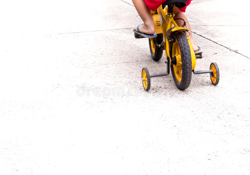Children with slippers cycling bike with training wheels. To prevent falls royalty free stock image