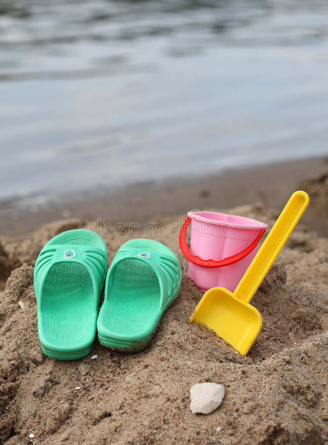 Children slippers and toys on beach royalty free stock photo