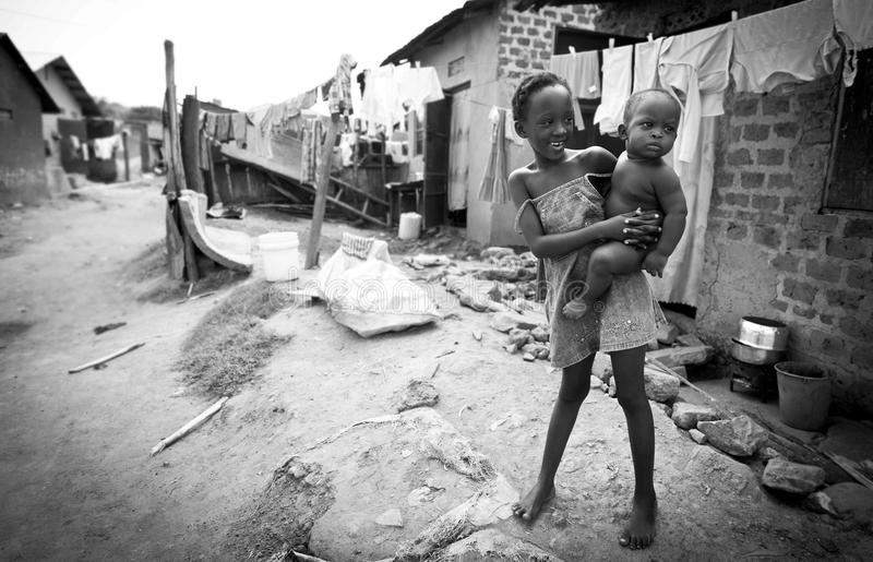Children in the slums of Kampala. A young girl and her sibling photographed in the slums of Kampala. Despite the conditions both appear happy and smiling royalty free stock photography