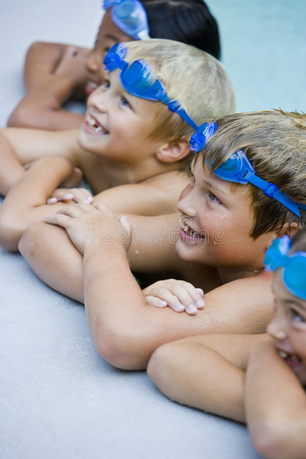 Children smiling, hanging on side of swimming pool stock image