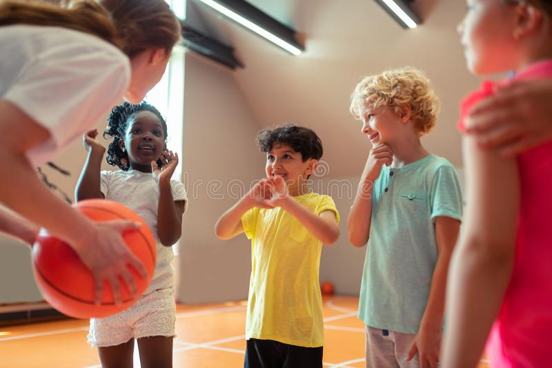 Children smiling to their sports teacher in the gym. Best teacher. School children smiling to their sports teacher playing basketball in the gym royalty free stock images