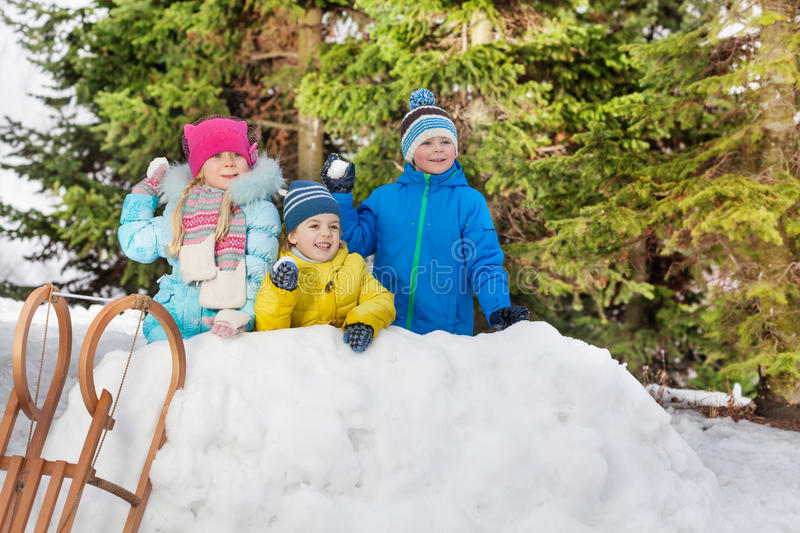 Children in snow fortress play snowball fight royalty free stock photos