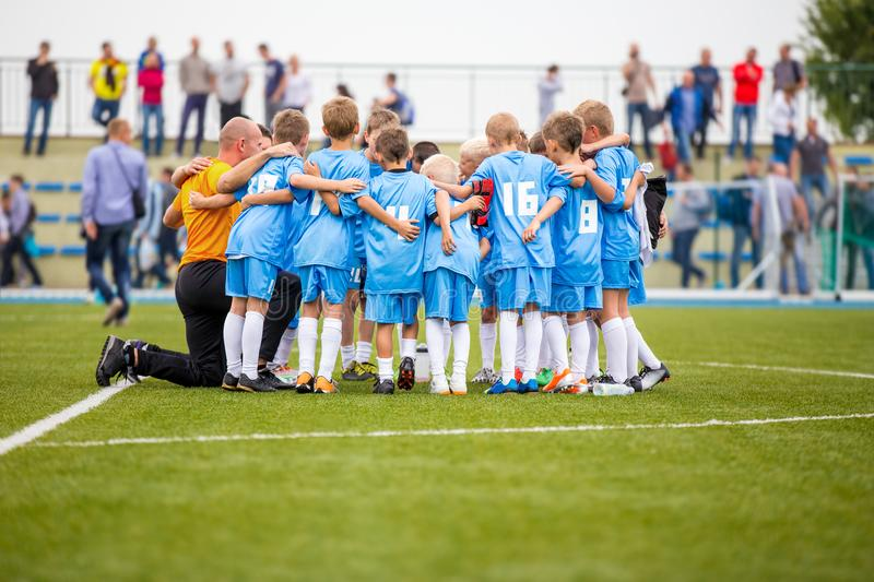 Children soccer football team with coach. Group of kids standing together on the pitch. Coach giving children`s soccer team instru royalty free stock photos