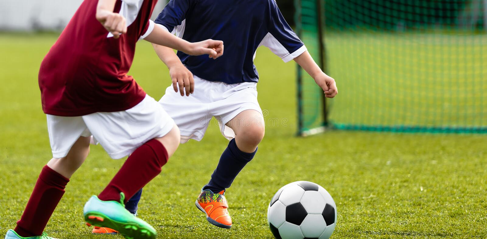 Children soccer game. Kids kicking soccer ball on a sports grass field. Children running after the ball stock image
