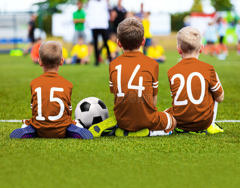 Children Soccer Team Playing Match. Football Game for Kids. Young Soccer Players Sitting on Pitch. Little Kids in Blue and Orange royalty free stock photo