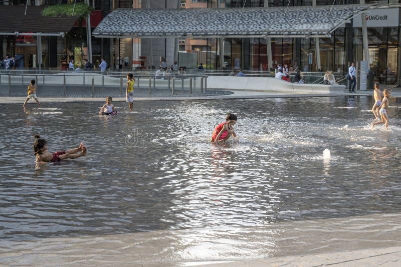 Children splashing and bathing ing at business hub, Milan stock photo