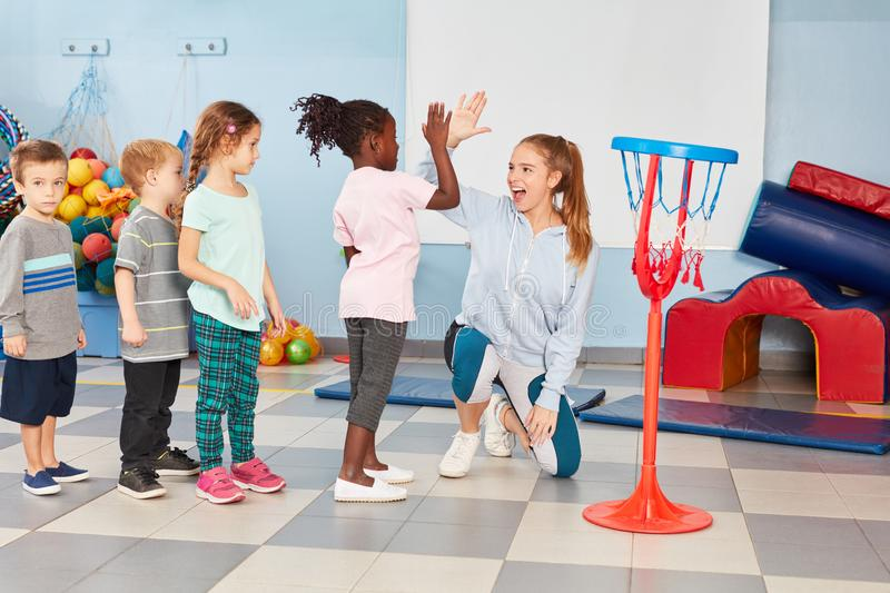 Children and sports teacher make high five. After the basketball training in the gym royalty free stock photography