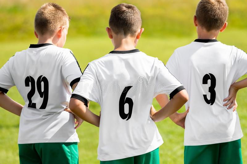 Children Sports Team Wearing White Soccer Jersey Shirts. Young Boys Watching Soccer Match. Football Tournament Competition royalty free stock image