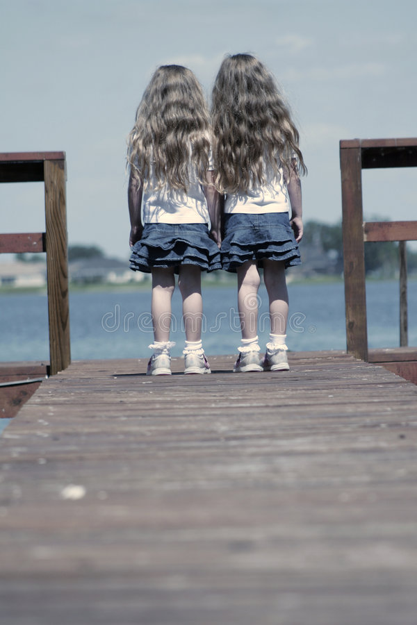 Children standing on end of dock stock photos