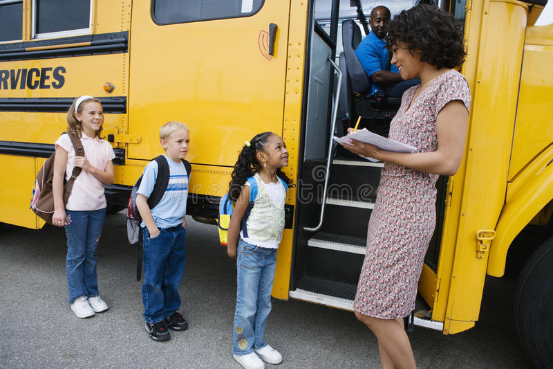 Children Standing In A Line By School Bus stock photo