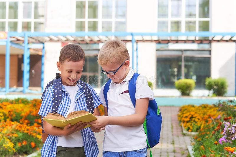 Children students communicate in school. Children students communicate.students read a book. positive primary school students in the school yard on the royalty free stock image