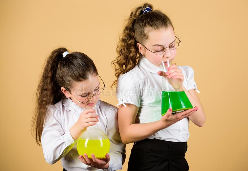 Children study at biology lesson. little smart girls with testing flask. knowledge and education. science research in stock photos