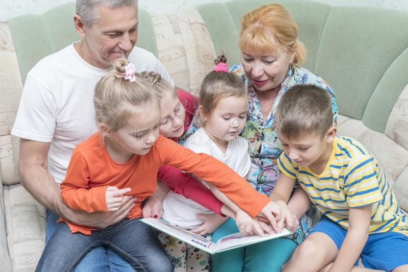 Children study book with grandparents stock images